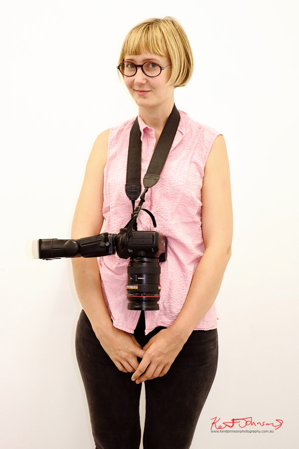 Round glasses, pink seersucker sleeveless shirt, black jeans and camera with lens 'bling'.