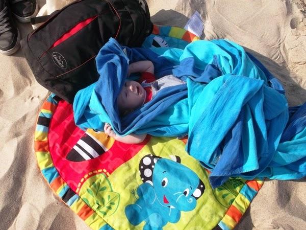 dziecko przykryte chustą nad morzem