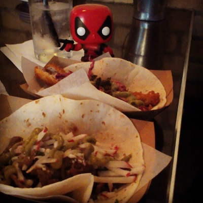 Tiny Deadpool stands behind two soft tacos in paper serving boats. The closer taco contains beef topped with julienned radish and green sauce, while the further taco is crispy fish garnished with red slaw and green sauce.