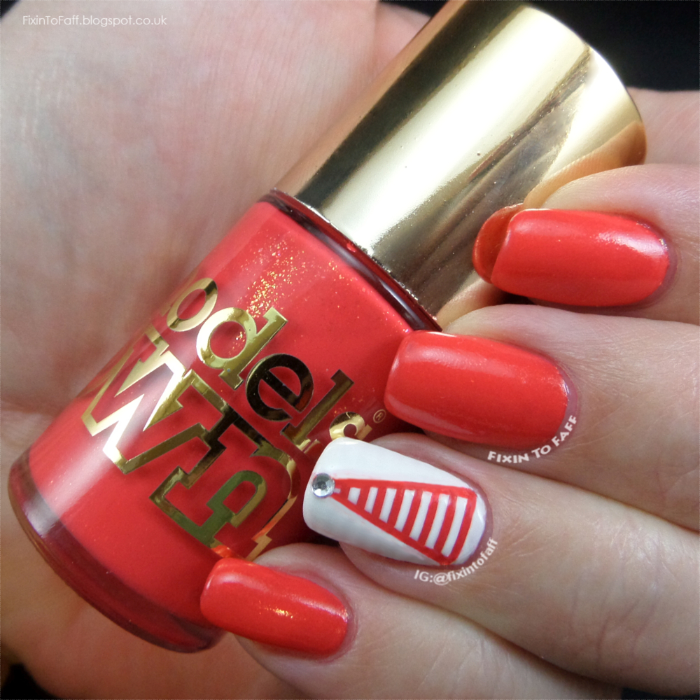 Models Own Diamond Luxe Carat Coral swatch with striping tape and rhinestone nail art accent.