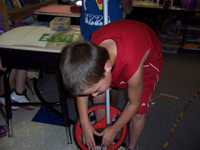 A student is working with the measuring wheel.