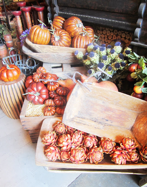 Fesitval fall arrangement with pumpkins, artichoke, other fall vegetables and wood trays