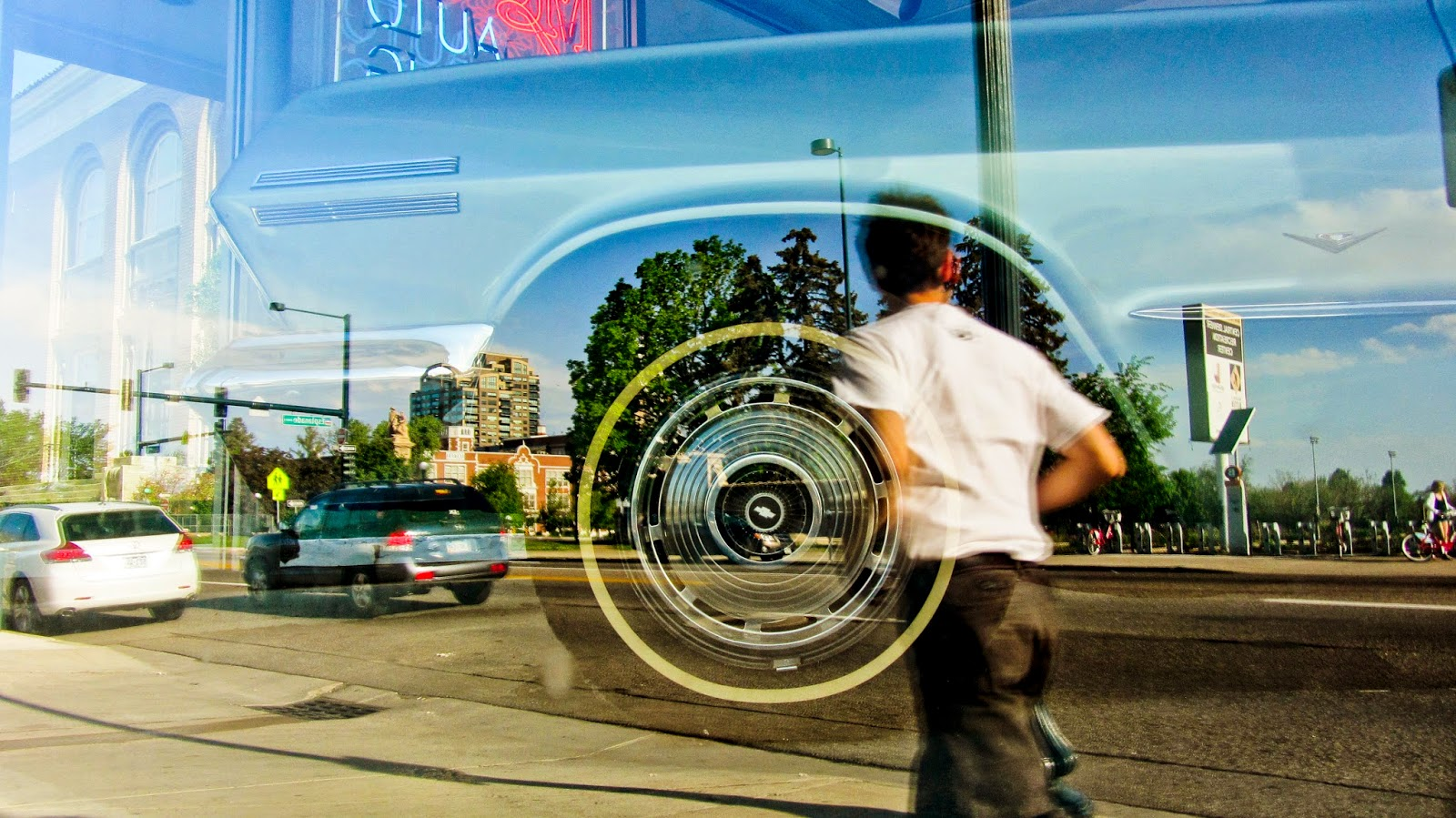 The wheel and hubcap of an old Chevrolet and a reflection of a Denver street scene.