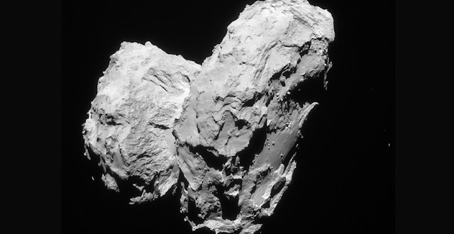 Two comets collided at low speed in the early Solar System to give rise to the distinctive 'rubber duck' shape of Comet 67P/Churyumov–Gerasimenko.  The image shown here was taken on 22 August 2014 at a distance of 63.4 km from the comet centre. It shows the comet's small lobe to the left, with the striking cliffs of Hathor clearly visible. In the foreground on the far right, the smooth Imhotep region can be seen on the large lobe. The image scale is 5.4 m/pixel and it measures 5.5 km across. Credit: ESA/Rosetta/Navcam – CC BY-SA IGO 3.0