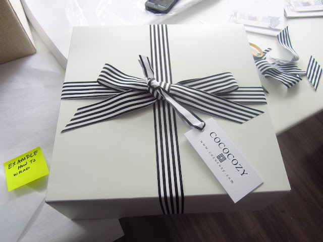 COCOCOZY gift box with black and white stripped ribbon on a white table at COCOCOZY HQ