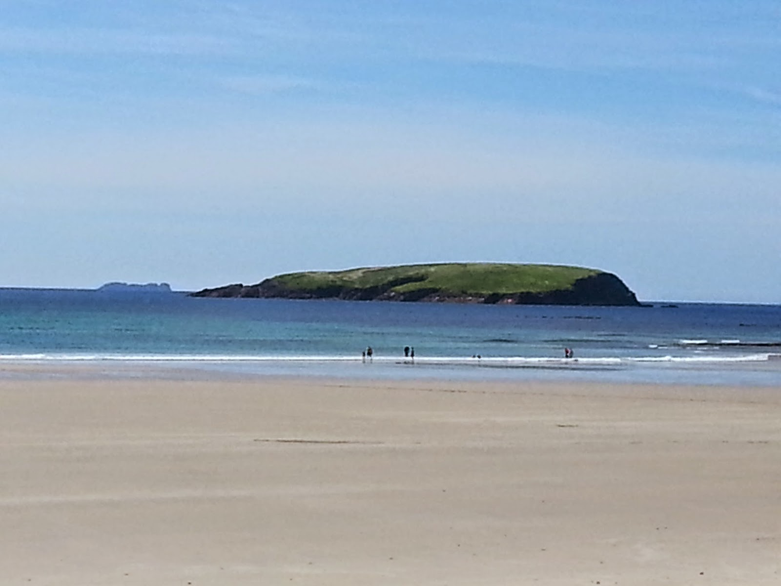 Keel beach in the foreground, Inisgalloon in the background, set against clear blue sky
