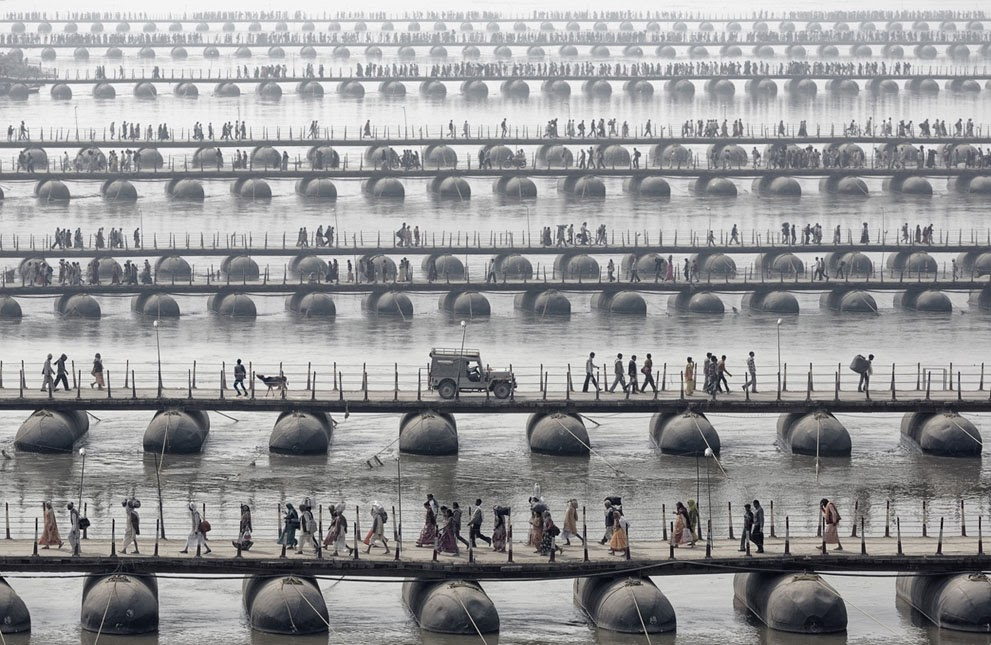 pilgrims and devotees cross pontoon bridges