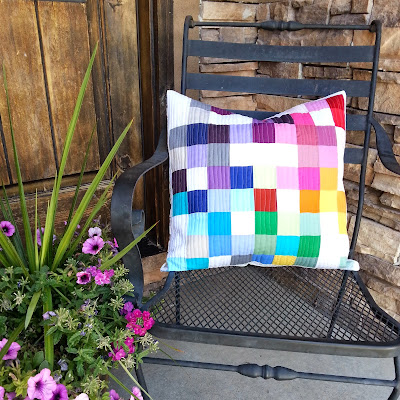 a pillow on a chair made with solid color squares in a rainbow of colors