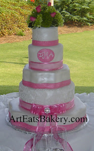 5 Tier white and pink fondant custom unique wedding cake design with ribbons, bow, and fresh flower