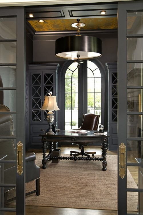 Dark gray walls accented with a gorgeous floral mural frame a home office furnished with a sapphire blue velvet chair placed at a long marble floating desk top.