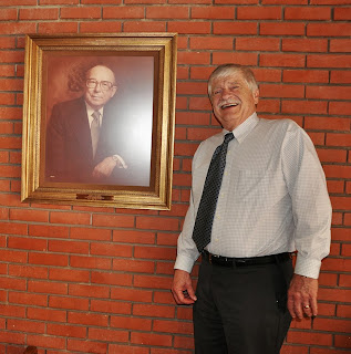Dr. Jerry Dowling stands next to a portrait of founding Dean Dr. George Killinger, who hired him in 1972.