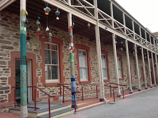 Colonial two-story building with a verandah and balcony across the front of it.  The supporting posts and balustrades are wooden and decorated with yarnbombing.