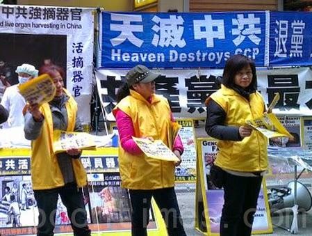 (图)香港青关会成员穿上黄衣服冒充法轮功学员,派发污衊法轮功的单张,欺骗市民,做法卑劣。(潘在殊/大纪元)