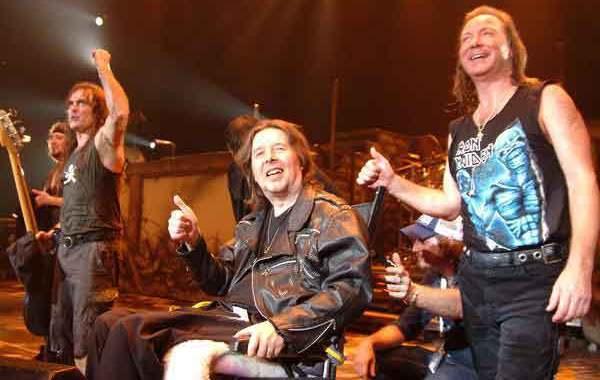 Clive Burr en silla de ruedas con los miembros de Iron Maiden