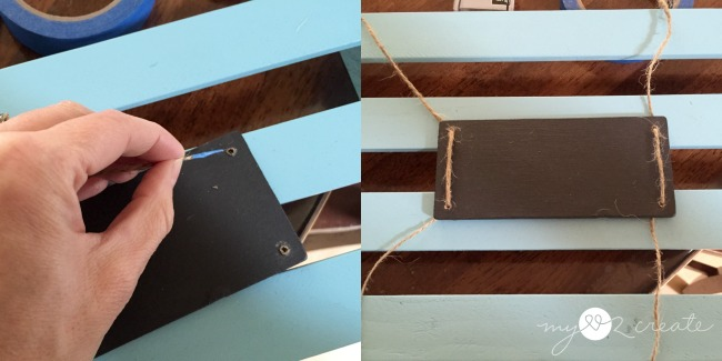 threading twine into chalkboard label to attach to magazine rack