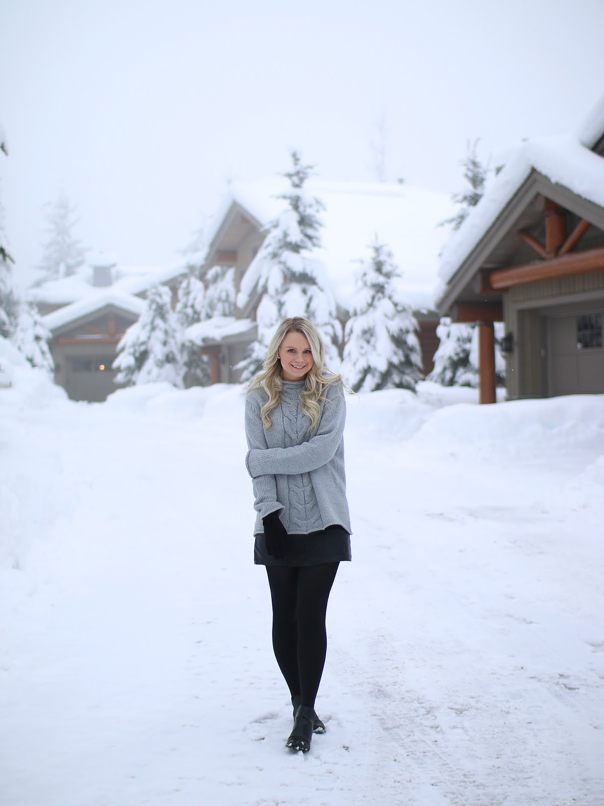 a winter wonderland in whistler canada, a women wearing a trendy neutral outfit in the snow