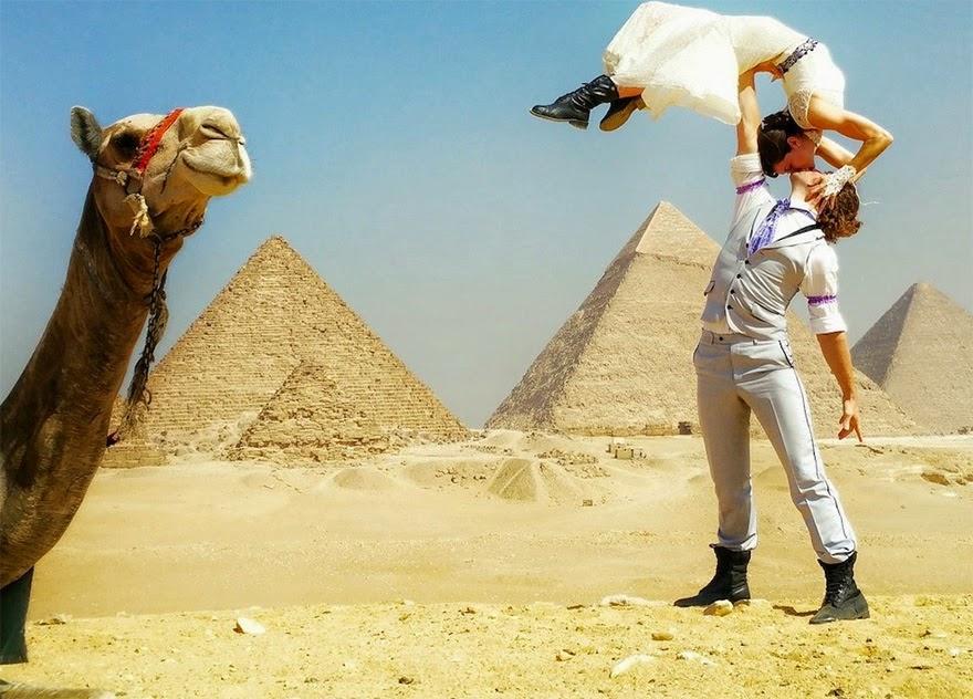 A foto retrata no deserto sob céu claro: na lateral esquerda, parte da cara e o longo pescoço de um camelo e à direita, um casal. O homem está em pé, corpo alongado, braço esquerdo para baixo um pouco afastado da perna, com o braço direito esticado ao alto, equilibra a mulher com a palma da mão apoiada na parte de trás da cintura dela; ela está com o tronco contorcido em arco, pés no ar, mãos espalmadas nas faces dele em um beijo. Ele usa colete bege sobre camisa branca com as mangas dobradas, na camisa, no meio do braço, em ambos os lados, há uma faixa estreita bordada em lilás, gravata roxa e branca, calça bege e coturnos pretos; e ela usa um vestido branco longo com uma faixa escura na cintura, o rodado da parte inferior esvoaça, luvas brancas rendadas sem dedos e coturnos pretos. Ao fundo, três imponentes pirâmides.