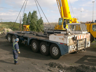 A crane lifts a crane carrier for loading