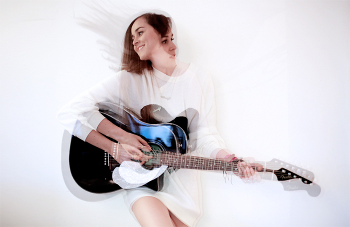 Fashion blogger Andy Torres playing her black Fender Sonoran guitar