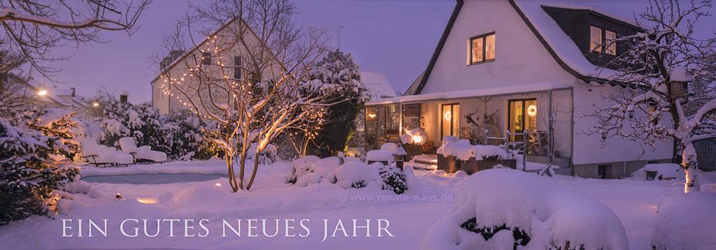 unser Garten im Winter bei Schneefall am Abend mit Beleuchtung