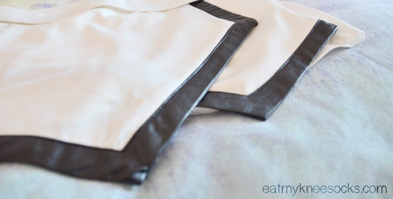 Close-up of the black leather trim on these white asymmetrical origami shorts from Romwe.