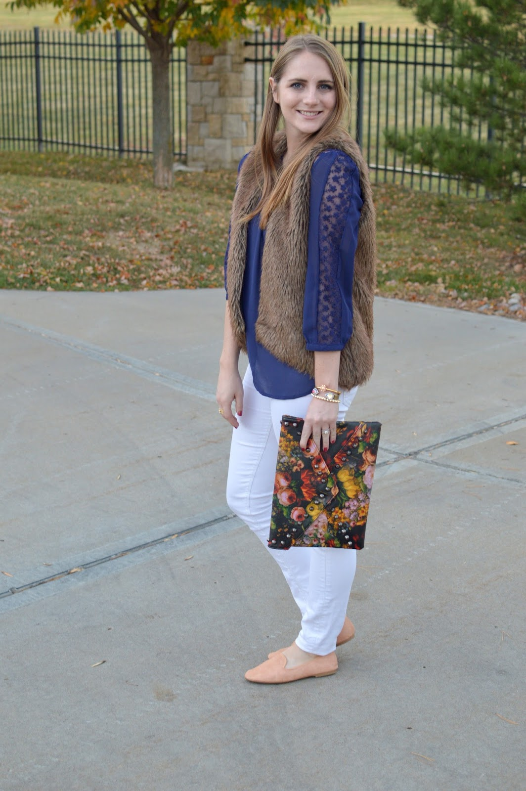 navy lace top with white jeans and a faux fur vest