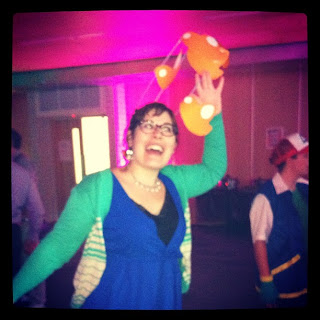 Me, dressed in a blue dress with green cardigan, holding a flock of orange paper birds over my head.