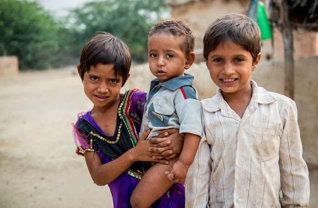3 children in a shepherd community in Rajasthan, India posing for a photograph