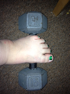 Photo of a steel 15lb dumbbell sitting on brown carpet with a pale foot resting on it