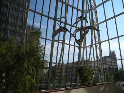 Stainless steel geese overhead inside a curtain wall atrium