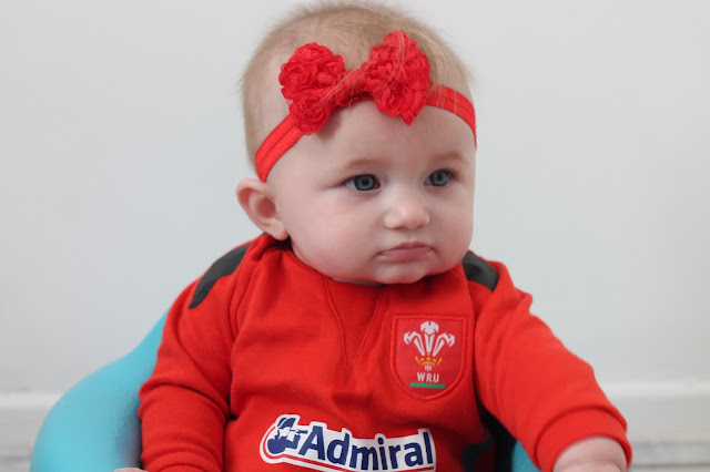 baby girl wearing Welsh rugby union sleepsuit and red headband