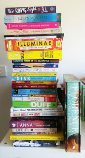 A photograph of a pile of about 30 books.