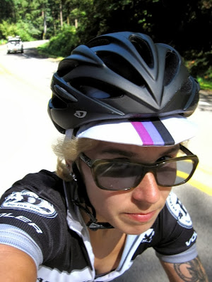 A selfie showing Halley on her bike with black helmet and sunglasses riding along a road in a forest
