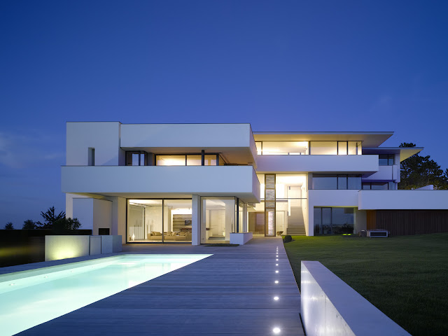 Photo of an amazing home at blue hour as seen from the pool area