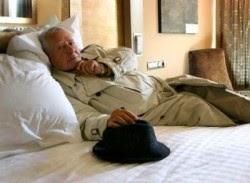 L'autor al llit, amb gavardina i barret a la mà
