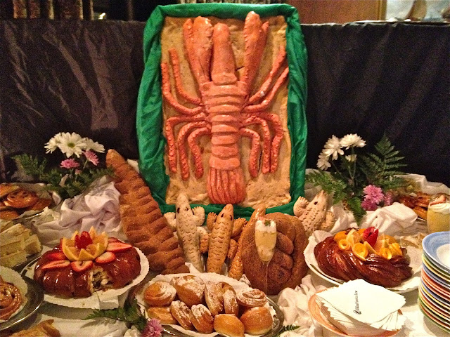 Lobster out of bread surrounded by desserts