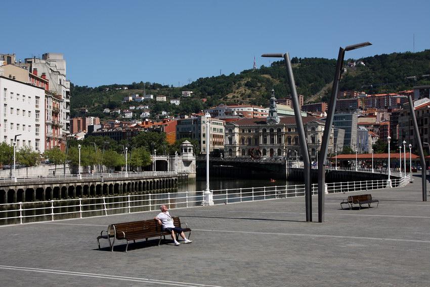 Zona de lazer junto ao rio. Um homem num banco a apanhar sol. Prédios ao fundo e a seguir as montanhaso