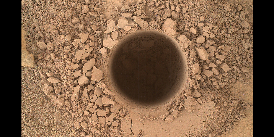 This image from the Mars Hand Lens Imager (MAHLI) camera on NASA's Curiosity Mars rover shows the first sample-collection hole drilled in Mount Sharp, the layered mountain that is the science destination of the rover's extended mission. Image Credit: NASA/JPL-Caltech/MSSS