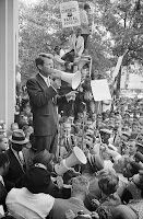 Bobby Kennedy with megaphone addressing hopeful and cheering crowd