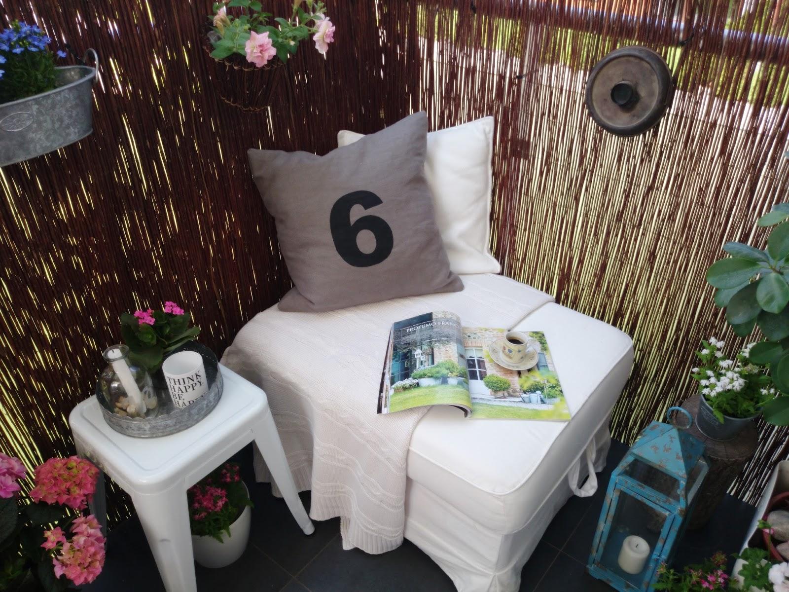 Turkusowy lampion z metalu, biały metalowy taboret, biała pufa na balkonie, lniana poduszka