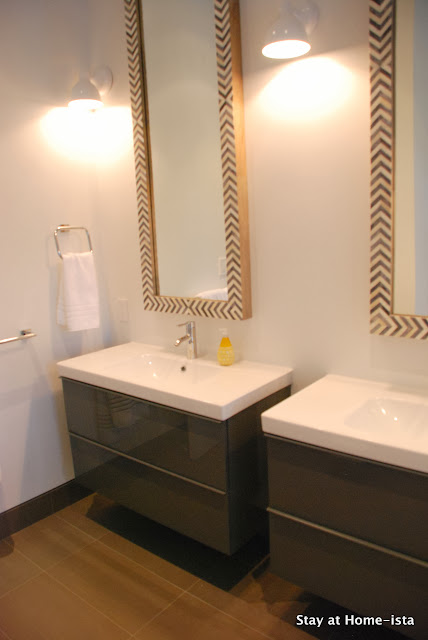 Modern grey and white bathroom with Ikea vanities and herringbone mirrors