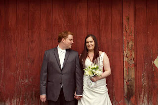 Bonnie and Joe stand in front of a red wall at the Courtyard Hall in Bothell