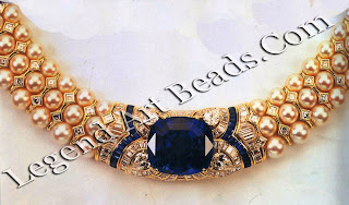 A necklace of cultured pearls and square-cut diamonds has as its central motif an 81.94-carat oval-cut sapphire with a pear-shaped diamond at each corner, set amid bands of baguette sapphires and diamonds.