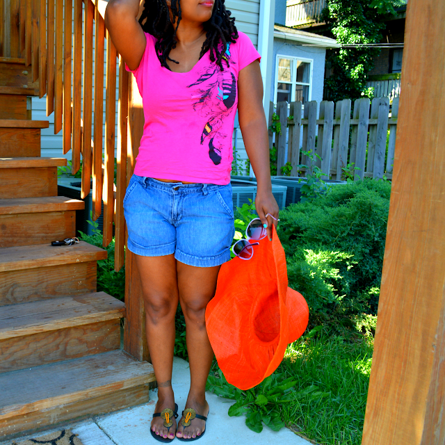 thrifted jean shorts worn with bright tee and sunhat