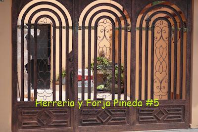 Hermosa puerta de hierro forjado, acabada en color cobre texturizado