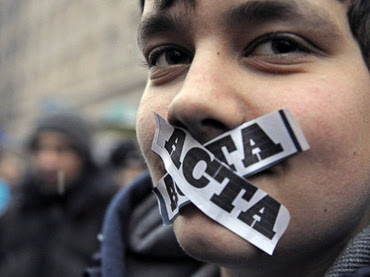 A demonstrator with ACTA stickers on his mouth takes part in a protest against Poland's government plans to sign international copyright agreement ACTA (Anti-Counterfeiting Trade Agreement), in front of the European Union office in Warsaw on January 24, 2012