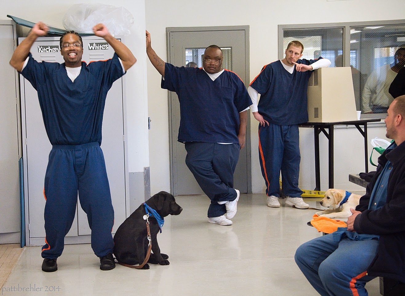 An african american man is doing jumping jacks to the left of a a young black lab puppy. The puppy is wearing a blue bandana and his leather leash is draped to the floor. The puppy is facing away from the man and looking to the right. Two other men are standing in the background to the right. Another man is sitting on the far right side, half out of view.