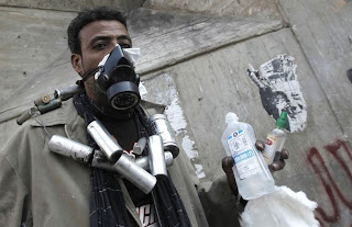 An Egyptian protester wears a gas mask to protect himself
