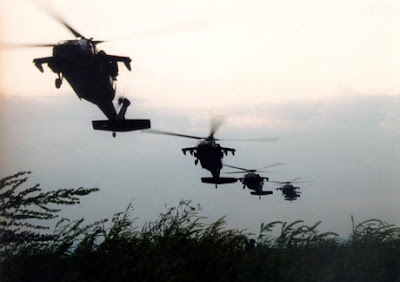 four Black Hawk helicopters in flight