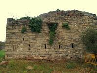 El mur de migdia del Fortí de la Rampinya amb les dues fileres d'espitlleres i una de les obertures per als canons